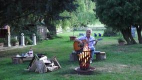 Молодая женщина играя акустическую гитару пока сидящ около лагерного костера акции видеоматериалы