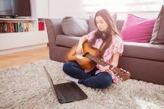 Молодая женщина играя акустическую гитару Стоковые Изображения RF