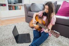 Молодая женщина играя акустическую гитару Стоковое Изображение RF