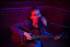 Молодая женщина играя гитару и поя mic в неоновом освещении стоковое изображение