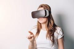 Молодая женщина играя игру в стеклах виртуальной реальности, использует цифровой экран касания виртуальной реальности управлением стоковые изображения rf