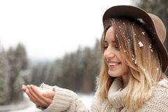 Молодая женщина играя со снегом outdoors Зима стоковое изображение