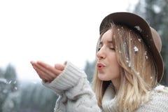 Молодая женщина играя со снегом outdoors стоковые изображения