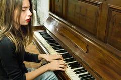 Молодая женщина играя старый винтажный рояль с смотреть прочь Стоковые Изображения RF