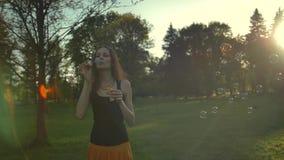Молодая женщина играя с пузырями мыла, внешними имеющ потеху E видеоматериал