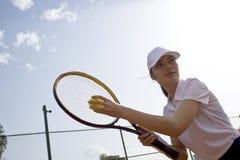 Молодая женщина играя теннис на суде стоковое изображение