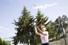 Молодая женщина играя теннис на суде стоковые изображения rf