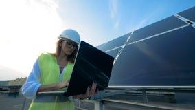 Молодая женщина идет при компьтер-книжка, смотря панели солнечных батарей 4K сток-видео