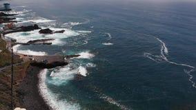 Молодая женщина идет против фона океана, волны падает на красивое побережье Тенерифе Живописный видеоматериал