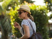 Молодая женщина идет ходить по магазинам в городе Девушка в стеклах, шляпе и striped футболке стоковая фотография