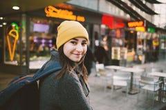Молодая женщина идет через улицу с неоновыми вывесками Перемещение, о стоковое фото