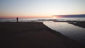 Молодая женщина идя вдоль пляжа смотря заход солнца и морскую воду - Tuja акции видеоматериалы