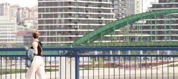 Молодая женщина идя за мост города и смотря панораму городского пейзажа стоковое изображение
