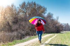 Молодая женщина идя и имея потеха с зонтиком стоковые изображения rf