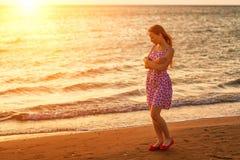 Молодая женщина идя на пляж на заходе солнца в солнечном свете стоковые изображения