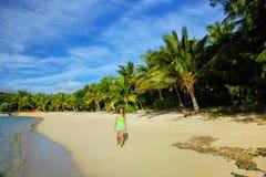 Молодая женщина идя на пляж на острове Drawaqa, островах Yasawa, Фиджи стоковая фотография