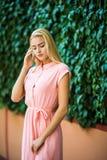 Молодая женщина идя на улицу идя в фиолетовое платье, на зеленой стене, предпосылка лист Стоковые Изображения RF