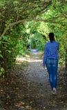 Молодая женщина идя через парк стоковая фотография