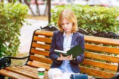 Молодая женщина изучая и писать в парке Стоковые Фото