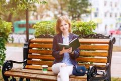 Молодая женщина изучая и писать в парке Стоковые Изображения