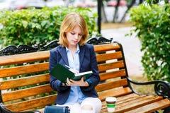 Молодая женщина изучая и писать в парке Стоковое фото RF