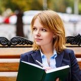Молодая женщина изучая и писать в парке Стоковая Фотография