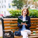 Молодая женщина изучая и писать в парке Стоковые Изображения RF
