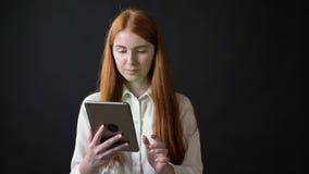Молодая женщина имбиря в белой рубашке держа таблетку с ключом chroma и показывая большие пальцы руки вверх, изолированный на чер видеоматериал