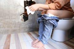 Молодая женщина имеет запор или геморрои сидя на туалете, h стоковые изображения