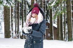 Молодая женщина имеет снежный ком в ее руке стоковая фотография rf