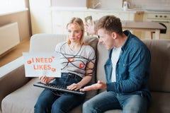Молодая женщина имеет социальную наркоманию средств массовой информации Сидеть на софе бесчувственной Тело в оболочке со шнуром Р стоковые изображения