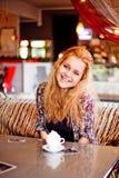 Молодая женщина имея обед на смеяться над кафа стоковая фотография