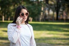 Молодая женщина имея переговор на ее smartphone стоковое фото rf