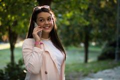 Молодая женщина имея переговор на ее smartphone стоковые изображения