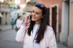 Молодая женщина имея переговор на ее smartphone стоковое изображение