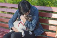 Молодая женщина имея полезного время работы с мопсом на зеленой траве, милой девушке с игрой собаки в парке во время захода солнц Стоковое Фото