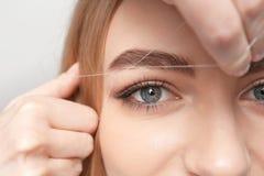 Молодая женщина имея профессиональную коррекцию брови стоковое фото