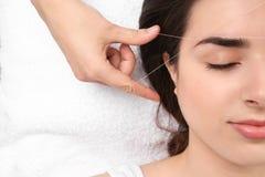 Молодая женщина имея профессиональную коррекцию брови стоковые фотографии rf