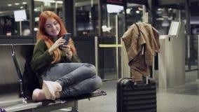 Молодая женщина использует телефон в крупном аэропорте