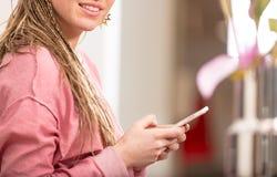 Молодая женщина используя ее мобильный телефон внутри помещения Стоковая Фотография