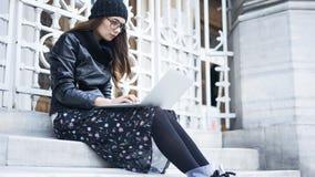 Молодая женщина используя компьтер-книжку внутри outdoors Стоковые Фото