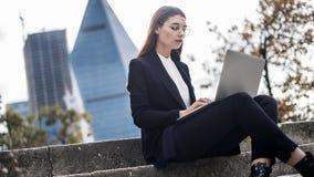 Молодая женщина используя компьтер-книжку внутри outdoors Стоковое Изображение RF