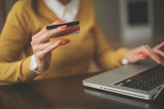 Молодая женщина используя компьтер-книжку и кредитную карточку конец вверх стоковая фотография