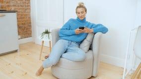 Молодая женщина используя смартфон дома сток-видео