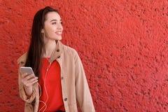 Молодая женщина используя телефон для слушать к музыке Стоковые Фотографии RF
