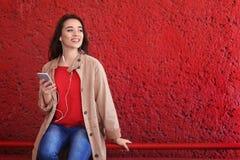 Молодая женщина используя телефон для слушать к музыке Стоковые Изображения