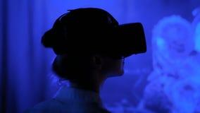 Молодая женщина используя шлемофон виртуальной реальности на темной взаимодействующей выставке сток-видео