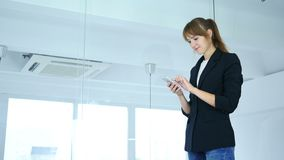 Молодая женщина используя smartphone для онлайн просматривать, задний взгляд видеоматериал