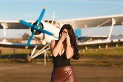 Молодая женщина испуганная для того чтобы лететь самолет для путешествовать Стоять около старого самолета закрывает ее сторону с  стоковые изображения rf
