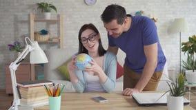 Молодая женщина и взгляд молодого человека на глобусе видеоматериал